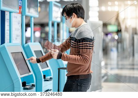 Asian Man Tourist Wearing Face Mask Using Self Check-in Kiosk In Airport Terminal. Coronavirus (covi