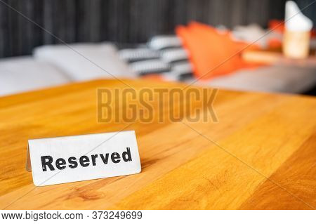 Metallic Reserved Sign Place On The Table In Restaurant