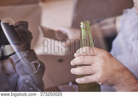 An Unrecognizable Man Drinking Beer While Driving Car. Concepts Of Driving Under The Influence, Drun
