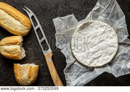 Brie cheese. White soft cheese with white mold with baguette on kitchen table. Top view.
