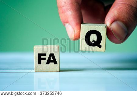 Faq Symbol. Word Faq On Wooden Cube. Hand Hold One Cube. Frequently Question Site.