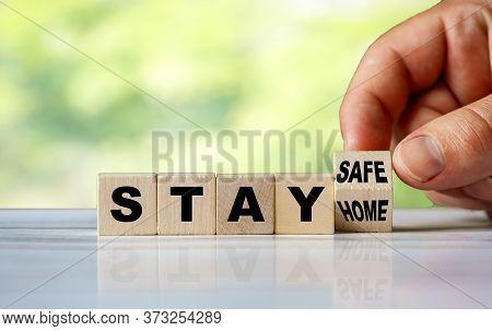 The Hand Turns The Wooden Cube And Changes The Word Stay Home To Stay Safe. Coronavirus Concept Back