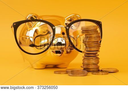 Golden Piggy Bank Wearing Glasses With Money Towers. Stack Of Euro Coins Near Golden Money Box. Mone