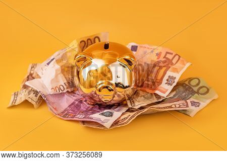 Golden Piggy Bank With Cash Money, Euro And Dollar Banknotes. Golden Money Box, Huge Savings, Money