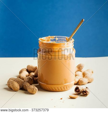 An Open Jar Of Peanut Butter With A Spoon And Peanuts In The Shell Around. Breakfast, Food For Veget