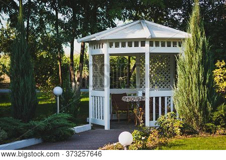 White Wooden Arbor On The Street In A Green Park. A Cozy Place To Spend Time.