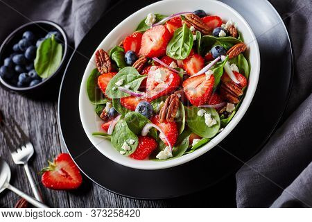 Summer Salad Of Strawberries, Blueberries, Spinach, Pecan Nuts And Crumbled Feta Cheese In A White B