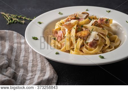 Close Up Pasta Fettuccine With Mushrooms, Bacon, Parmesan Cheese In White Plate With Napkin On A Dar