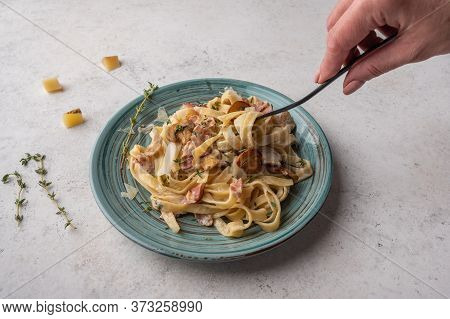 Womans Hand Holds A Fork With Pasta Fettuccine With Mushrooms, Bacon And Parmesan Cheese In Plate On