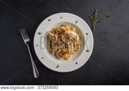 Top View Pasta Fettuccine With Mushrooms, Bacon And Parmesan Cheese In White Plate On A Dark Graphit