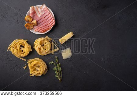 Top View Ingredients Of Pasta Fettuccine With Mushrooms, Bacon And Parmesan Cheese. Raw Food On A Da