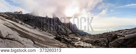 Climbers Trek Down The Rocky Slopes Of Mount Kinabalu At Sunrise, In Borneo, Malaysia