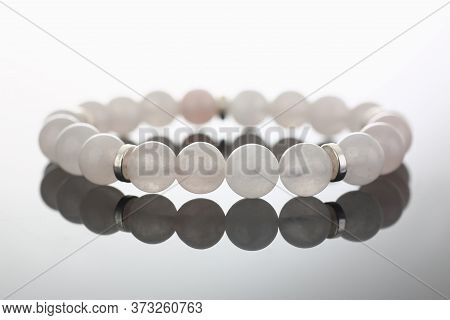 Close Up Of White Bead Stretch Bracelet Jewelry Reflecting On Glass Surface