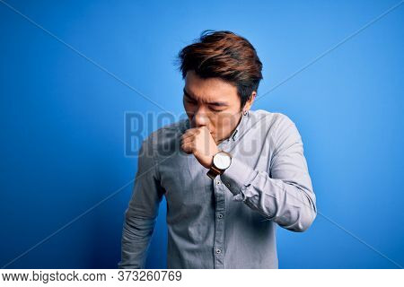 Young handsome chinese man wearing casual shirt standing over isolated blue background feeling unwell and coughing as symptom for cold or bronchitis. Health care concept.