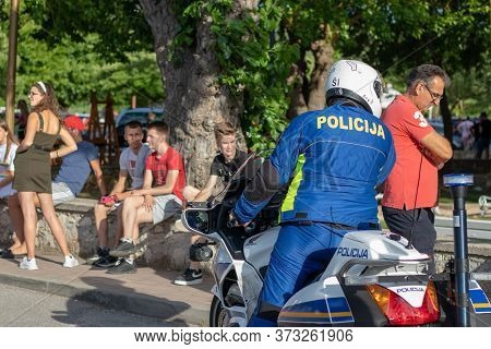 Skradin Croatia June 2020 Rear View Of A Croatian Police Officer On A Motorbike, Inspecting Local Pe