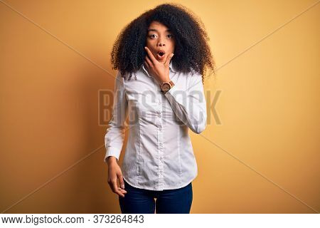 Young beautiful african american elegant woman with afro hair standing over yellow background Looking fascinated with disbelief, surprise and amazed expression with hands on chin