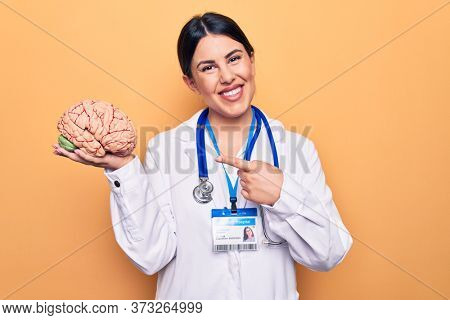 Young beautiful psychiatrist woman wearing stethoscope holding brain over yellow background smiling happy pointing with hand and finger