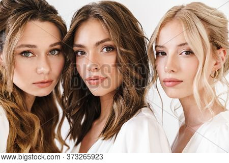 Photo of caucasian charming three women posing and looking at camera isolated over white wall