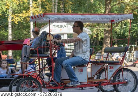 Moscow, Russia - Septmber 01, 2019: A Man And A Child Riding Car With Pedals In A City Park In Summe