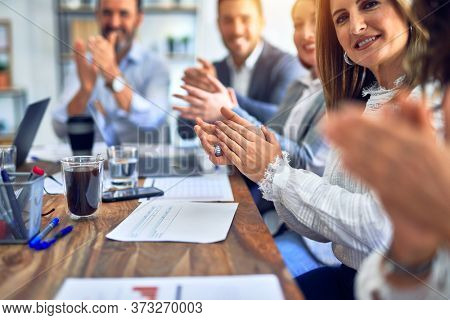 Group of business workers smiling happy and confident. Working together with smile on face looking at the camera applauding at the office