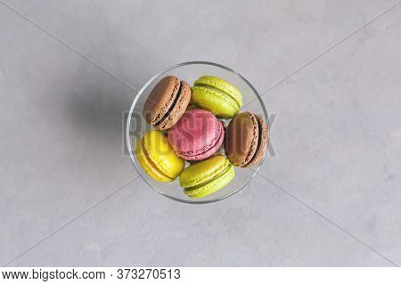 Tasty Multi-colored French Macaroons On A Grey Background. Pink, Green And Brown Macaroons. Place Fo
