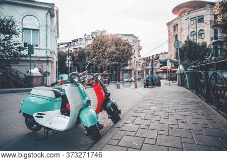 Two Moped Scooter Red And Blue In The Street Of Old Town Parked Near Sidewalk, Touristic City. Stree