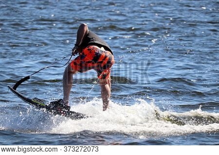 Jet Surfing On A Water, Man Riding On Jet Surfboard. Surfer On The Sea, Summer Sport