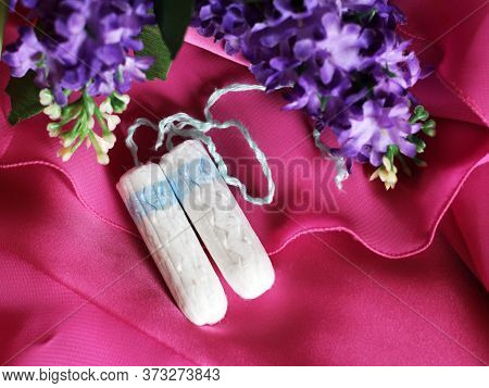 Tampon And Violet Flowers Jn A Pink Background, Top View
