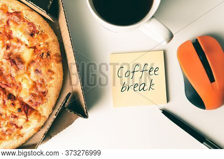 Pizza In Box, Cup Of Coffee, Laptop, Computer Mouse, Pen And Sticker With Text Coffee Break On Desk