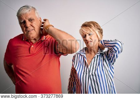 Senior beautiful couple standing together over isolated white background Suffering of neck ache injury, touching neck with hand, muscular pain