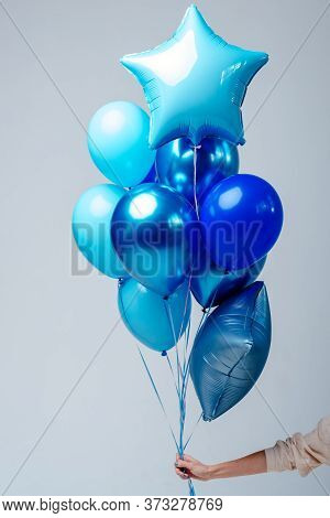 Composition Of Dark Blue, Blue, Transparent Helium Balloons And Two Sapphirine Star In The Hand Of A