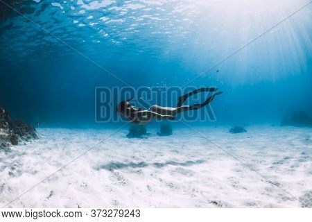 Sporty Woman Freediver With Fins Glides Over Sandy Bottom Near Corals Underwater In Ocean