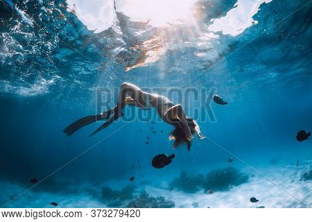 Free Diver Young Woman With Fins Glides Over Sandy Bottom With Tropical Fishes In Transparent Ocean