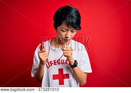 Young beautiful asian lifeguard girl wearing t-shirt with red cross using whistle feeling unwell and coughing as symptom for cold or bronchitis. Health care concept.