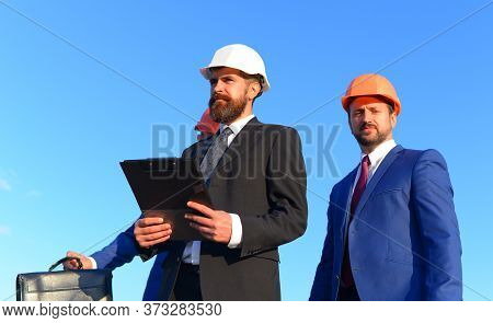 Engineers Inspect The Worksite On Blue Background. Builders Work Together