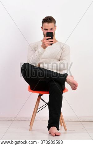 Man With Stylish Hair And Interested Face Holds Mobile Phone.