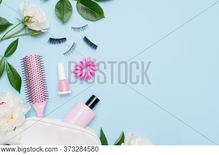 Top View Of Set Of Make Up And Skin Care Products Spilling Out Of Cosmetics Bag On Blue Background W