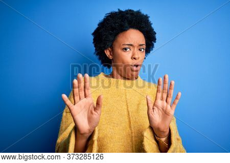 Young beautiful African American afro woman with curly hair wearing yellow casual sweater Moving away hands palms showing refusal and denial with afraid and disgusting expression. Stop and forbidden.