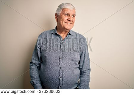 Senior handsome hoary man wearing casual shirt standing over isolated white background looking away to side with smile on face, natural expression. Laughing confident.