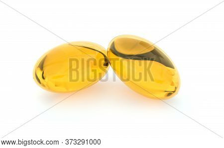 Two capsules with oil. Softgel with Omega 3, Vitamin D,E,A. Supplement capsules isolated on white background. Food supplement.