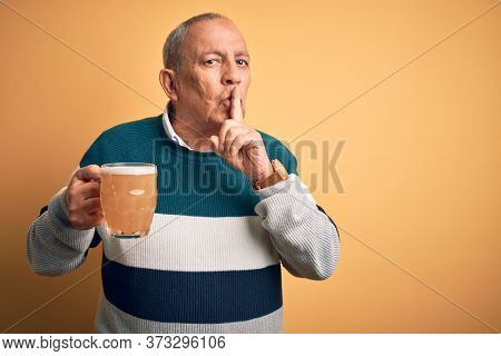 Senior handsome man drinking jar of beer standing over isolated yellow background asking to be quiet with finger on lips. Silence and secret concept.