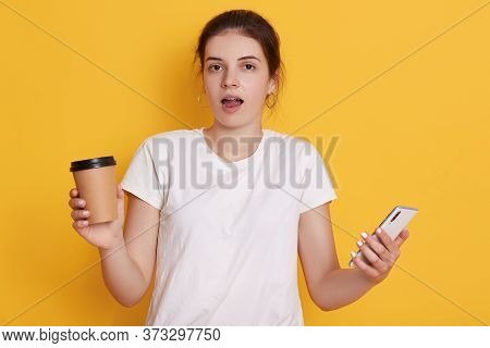 Astonished Lady With Opened Mouth Standing Against Yellow Background, Holding Smart Phone And Take A