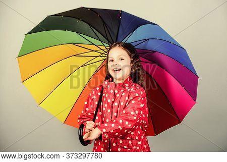 Enjoy Rain Concept. Fall Season. Kid Girl Happy Hold Colorful Rainbow Umbrella. Rainy Weather With P