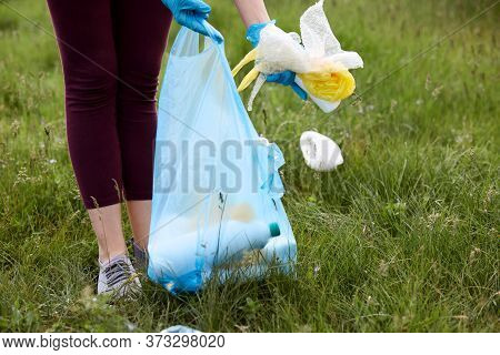 Faceless Person Wearing Burgundy Trousers Picking Up Litter From Green Grass And Putting Trash Into
