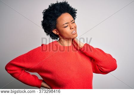 Young beautiful African American afro woman with curly hair wearing red casual sweater Suffering of neck ache injury, touching neck with hand, muscular pain