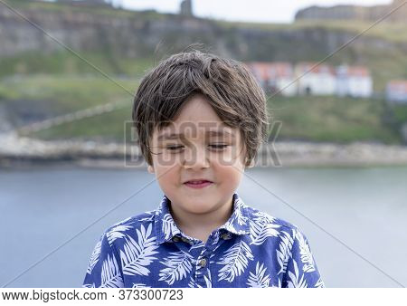 Head Shot Boy Face With Eyes Closed Standing Alone By The Sea, Happy Kid Laughing While Closing His
