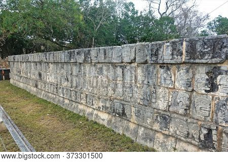 Ancient Ruins In Chichen Itza, Mexico. The Stone Platform Of The Skulls Is Decorated With Carvings I