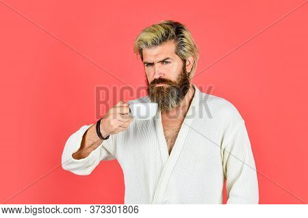 Breakfast Concept. Man With Beard In Bathrobe Enjoy Morning Coffee. Guy In Domestic Clothes Hold Cof
