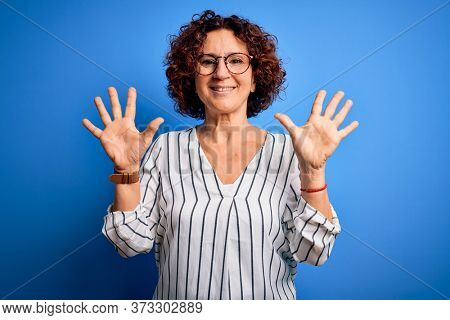Middle age beautiful curly hair woman wearing casual striped shirt over isolated background showing and pointing up with fingers number ten while smiling confident and happy.