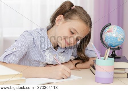 Education And School Concept. Child Is Sitting At The Desk And Writing.. Cute Little Student Girl Is